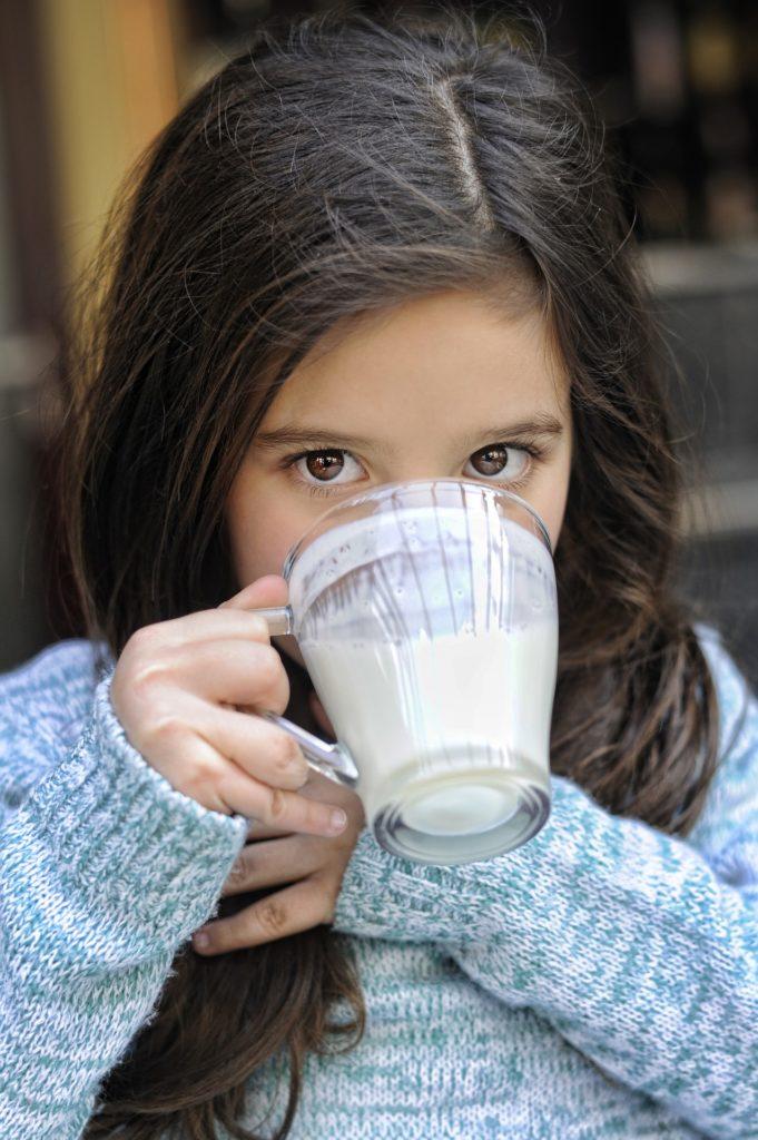 Fille qui boit un verre rempli de lait