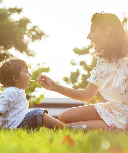 Mère qui donne à manger du yaourt à son fils